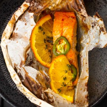 Salmon in parchment topped with oranges, jalapenos and thyme