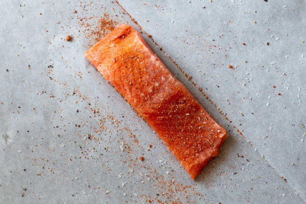 A salmon fillet seasoned with chile powder on a sheet of parchment paper