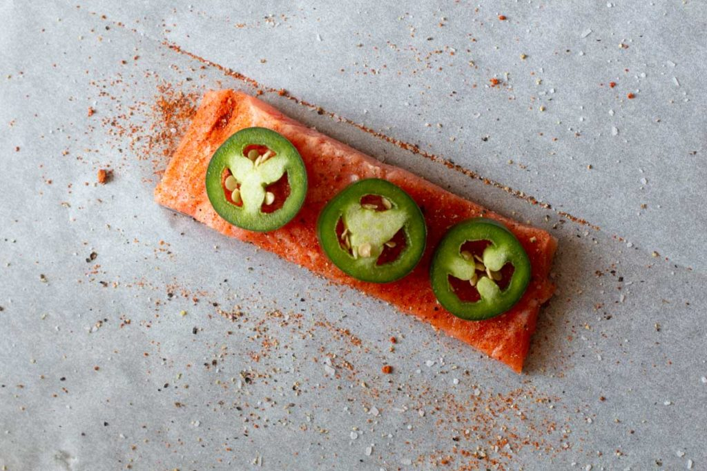 sliced jalapeno peppers on a salmon fillet on parchment paper