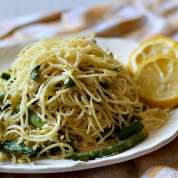 Angel Hair Pasta with asparagus and lemon cream sauce. Served on a white platter with slices of fresh lemons