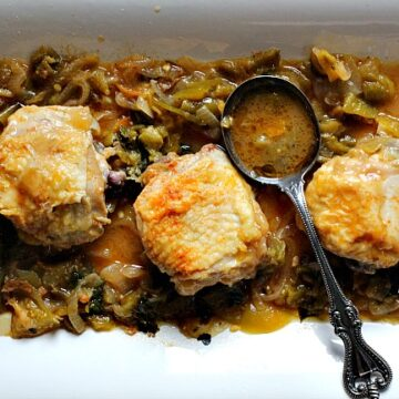 One pan crispy chicken thighs with tomatillo wine sauce on a white serving platter with an antique serving spoon