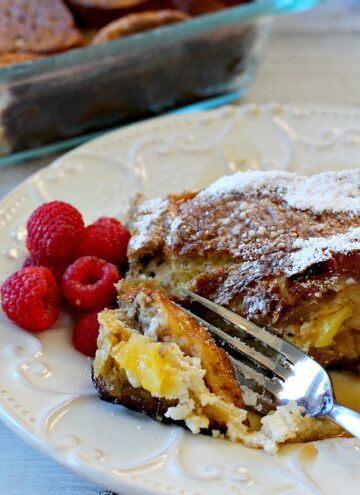A slice of mango cream cheese stuffed french toast with a side of fresh raspberries