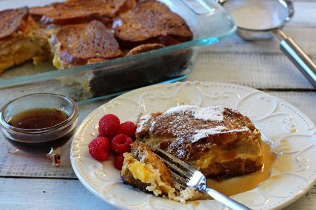 A fork cutting a slice of mango cream cheese stuffed french toast with a side of fresh raspberries