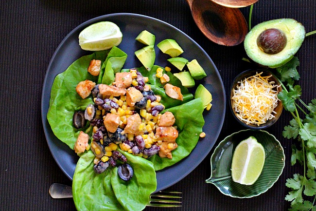 Mexican salad recipe served on bibb lettuce and topped with chicken, kidney beans, sweet corn, olives and avocado