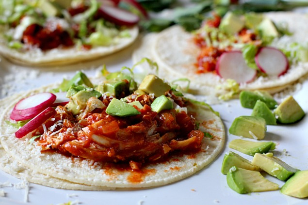 Chicken Soft tacos in a tomato sauce topped with chopped avocado and sliced radish.
