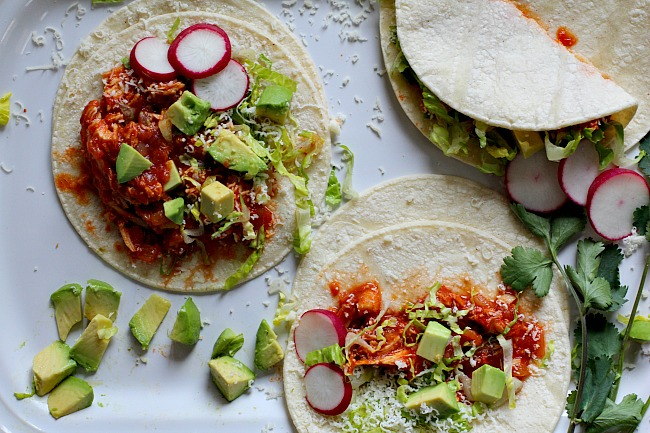 Warm flour tortillas filled with chicken and topped with romaine lettuce, radishes and avocado for chicken soft tacos.