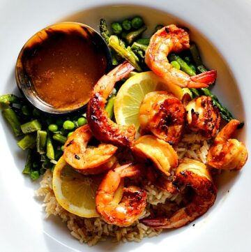The best grilled shrimp recipe served with asparagus peas and brown rice with a bowl of butter sauce