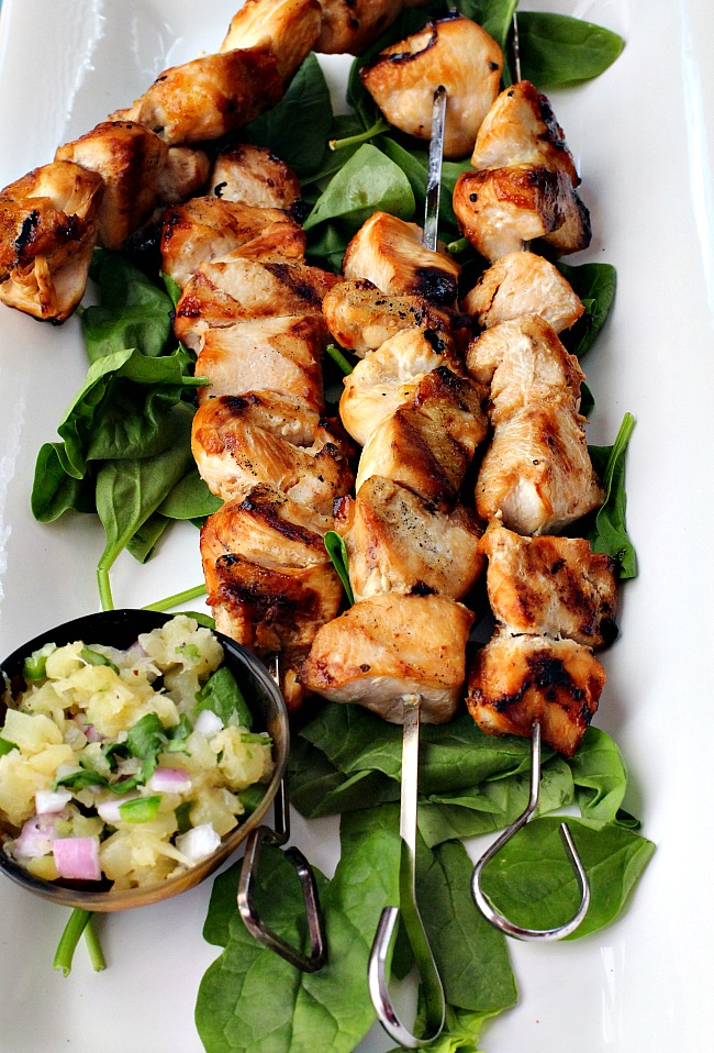A white platter filled with grilled chicken kabobs on a bed of fresh spinach and a bowl of jalapeno salsa