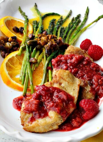 Chicken breast cutlets with raspberry sauce and asparagus spears with orange sauce