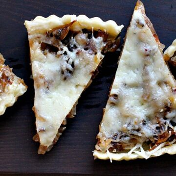 Caramelized Onion Tart with bacon and gruyere sliced and served on a wood cutting board.