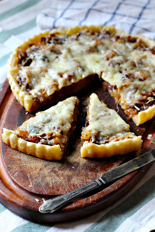 Caramelized onion tart with guyere cheese baked in a tart pan with homemade butter pie crust