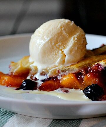 "peach blueberry pie in a 9"" tart pan with lattice topping and topped with a scoop of vanilla ice cream"