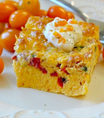 3-cheese egg casserole on white dish with heirloom cherry tomatoes