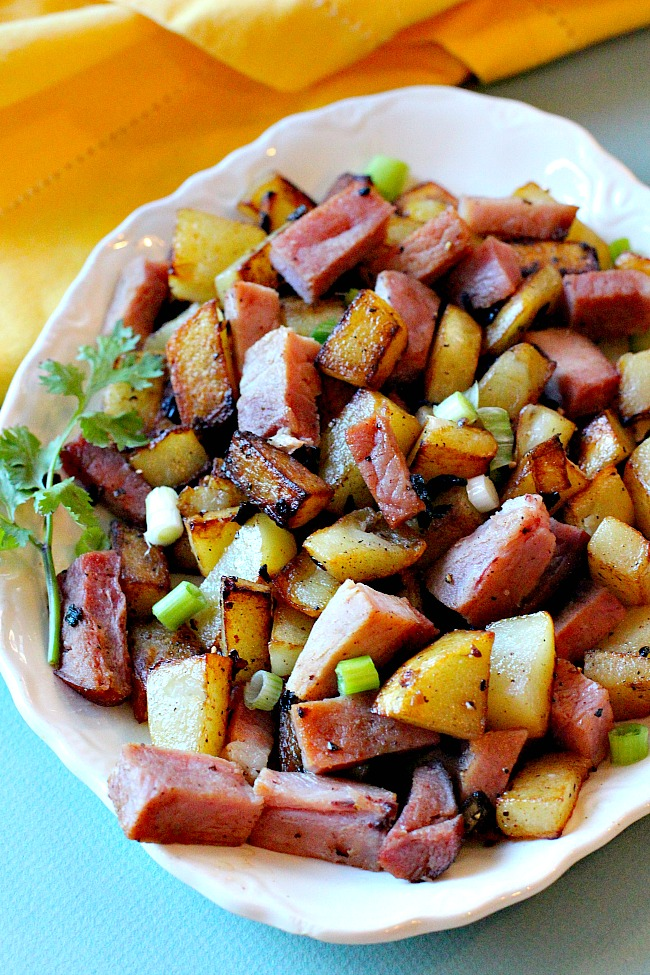 A platter of home fried potatoes with ham
