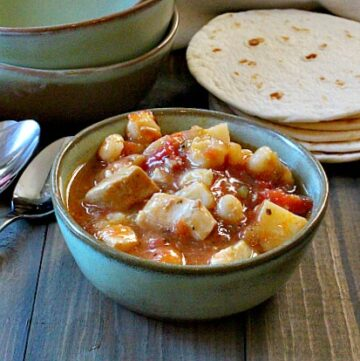 Pork green chile stew with potatoes and hominy and green chile. Served in Frankoma Green Soup Bowls with white flour tortillas.