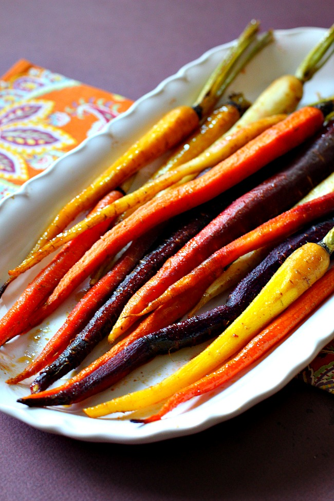 Oven roasted carrots glazed with cumin and lime on a Sur la Table white serving platter.