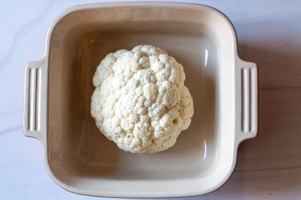 Whole head of cauliflower in a deep casserole dish ready to cook in the microwave