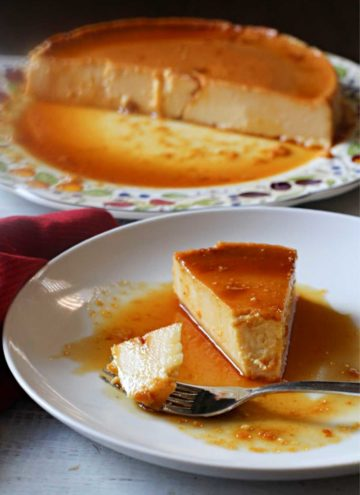 A slice of cream cheese flan with caramel sauce