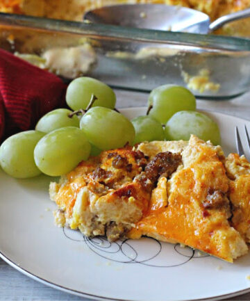 sausage egg cheese casserole on a vintage 1950's china plate with fresh green grapes