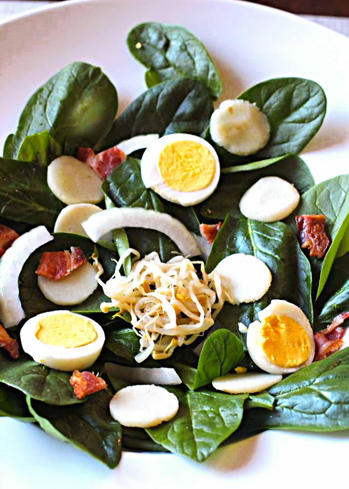 Spinach salad garnished with sliced hardboiled eggs and bacon