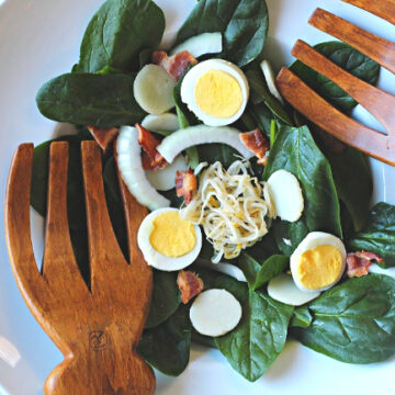 Crunchy spinach salad with bacon and wooden salad hands.