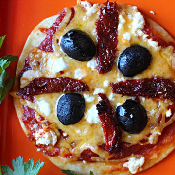 Tortilla pizza appetizer with cheddar cheese, goat cheese, sun dried tomatoes and black olives
