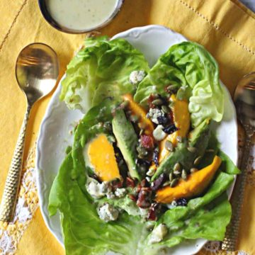 Avocado Mango Salad on a white platter topped with blue cheese