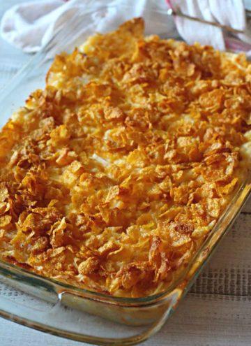 Cheesy potato casserole with corn flakes in a pyrex casserole dish