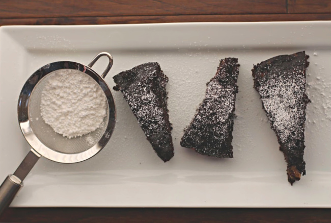 Chocolate banana bread recipe cut in wedges, sprinkled with powdered sugar on a rectangular white serving platter