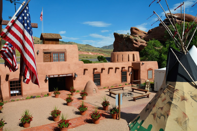 Photo of the outside of The Fort Restaurant in Denver with red rock formations in the back ground