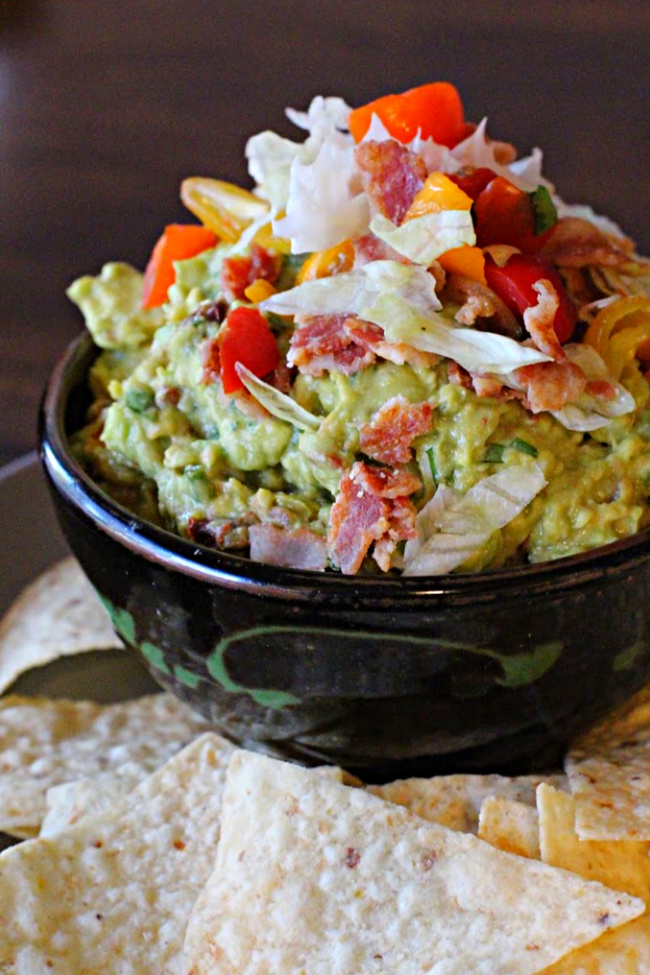 Spicy Guacamole Recipe with bacon lettuce and tomato served in a brown handmade pottery dish with tortilla chips alongside.