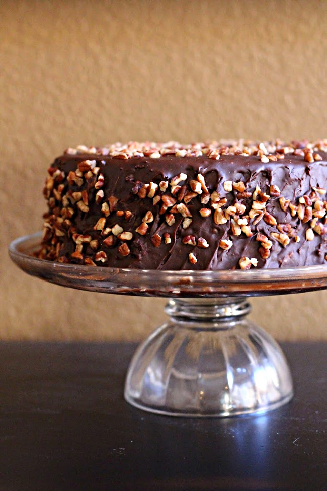 Chile Chocolate Cake on a glass cake stand. With bourbon chocolate frosting covered with pecans