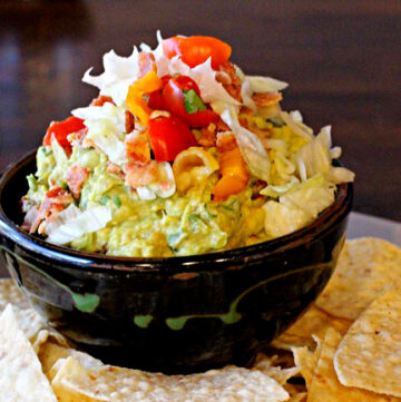 Spicy Guacamole recipe with bacon lettuce and tomato served in a brown pottery bowl with tortilla chips