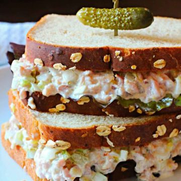 Homemade ham salad sandwich spread on oatnut bread topped with a pickle