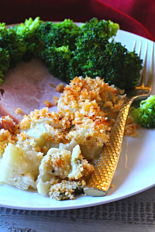 Instant Pot scalloped potatoes with green chile peppers on a white plate with ham and broccoli.