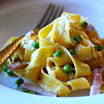 Pappardelle pasta with peas and ham and lemon cream sauce served in a white pasta bowl with a gold fork.