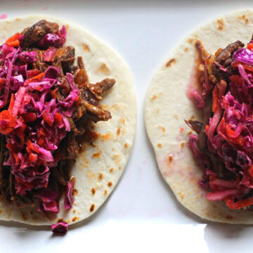 braised beef tacos on a white flour street taco shell topped with cabbage carrot slaw