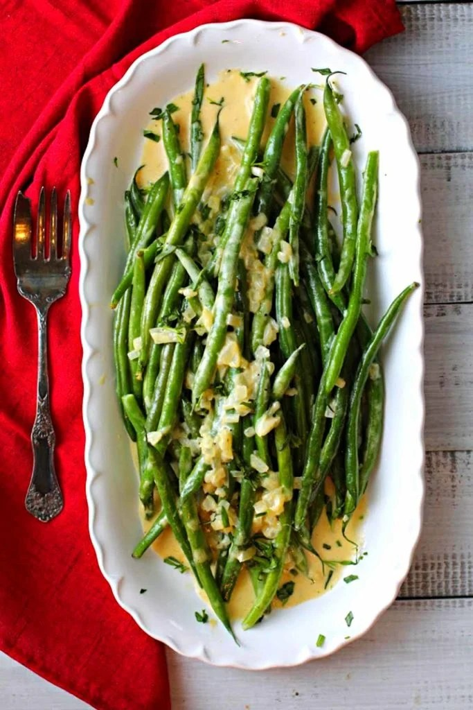Green beans with grainy mustard sauce served on a white platter