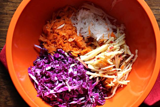 shredded Red cabbage, shredded carrot, shredded gala apple, shredded onion in an orange bowl.