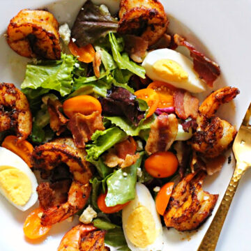 Blacked shrimp salad in a large wide rimmed salad bowl with hard boiled eggs, spring greens, and applewood smoked bacon. With champagne vinaigrette.
