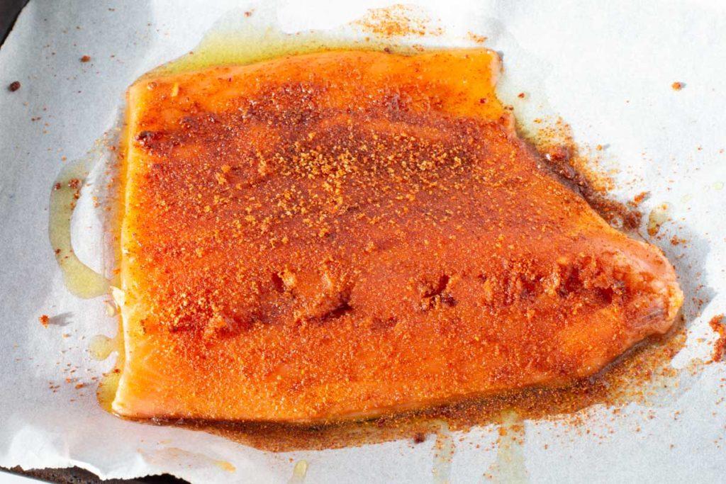 Adding a brown sugar chile powder rub to salmon fillet