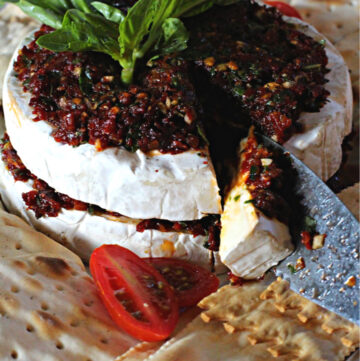 Two halves of a wheel of brie cheese to make stuffed brie appetizer.