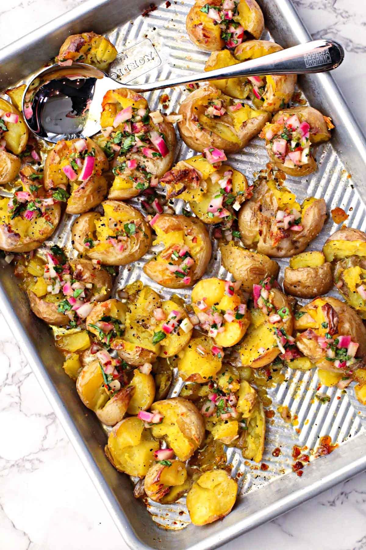 Smashed yukon gold potatoes with chimichurri sauce on a sheet pan