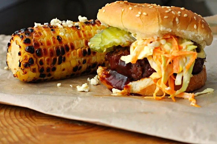 Texas burger recipe, a Bobby Flay recipe topped with homemade coleslaw, pickles and bbq sauce. Sided with grilled corn.