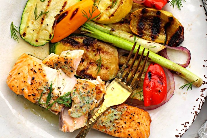 Easy grilled salmon fillets served with grilled vegetables on a rustic white plate