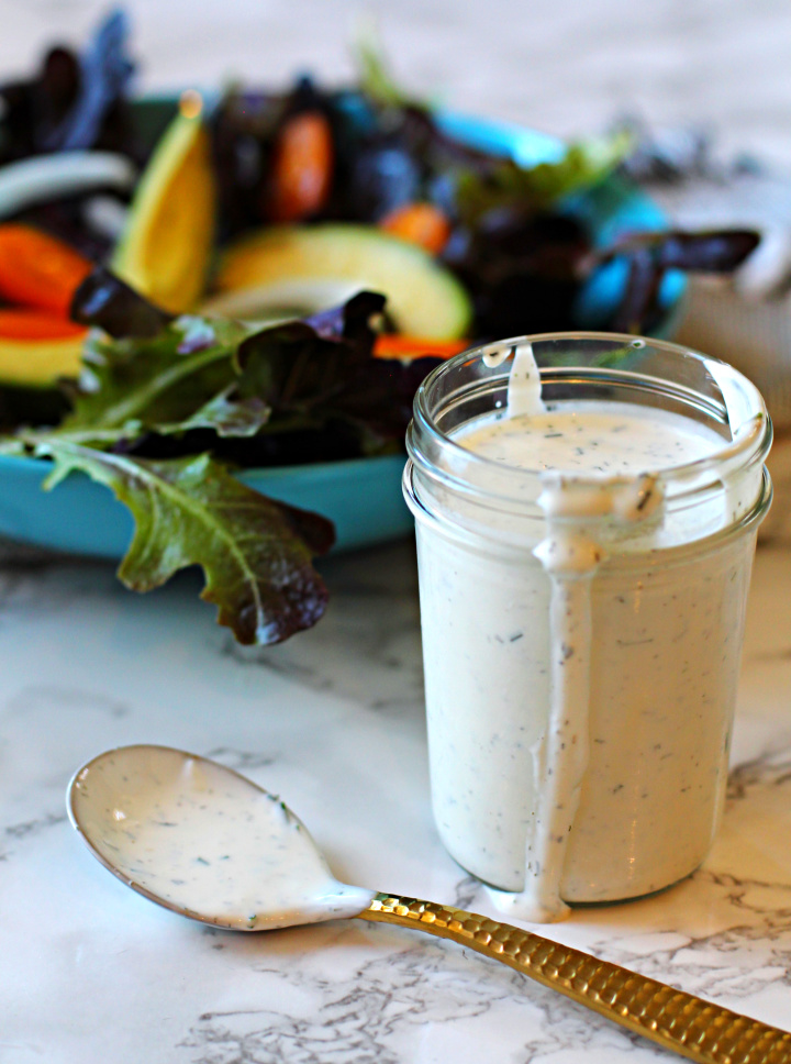 Homemade buttermilk dressing served in a mason jar. With a tossed salad with avocados.