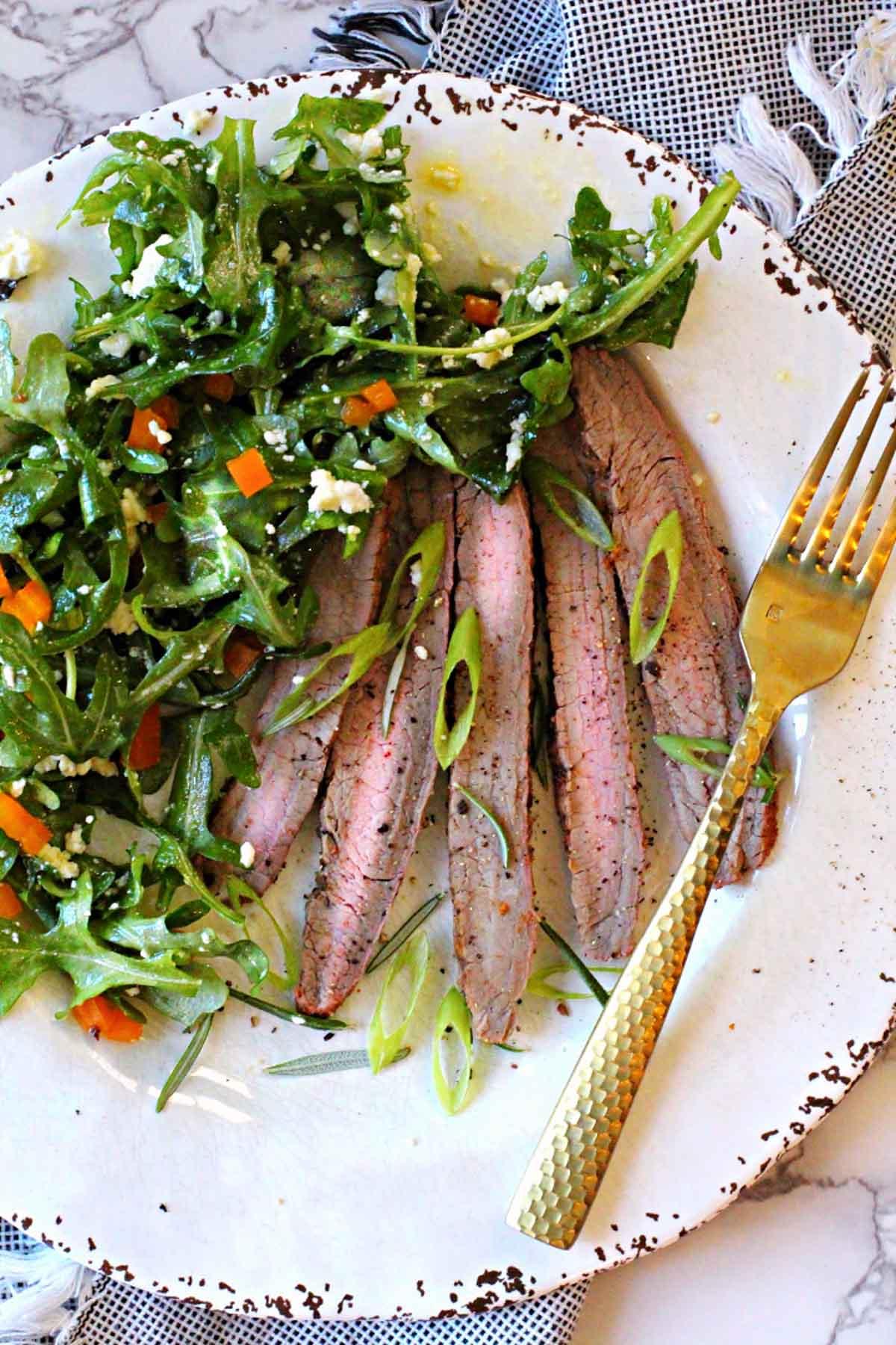 Sliced grilled flank steak served with a kale salad