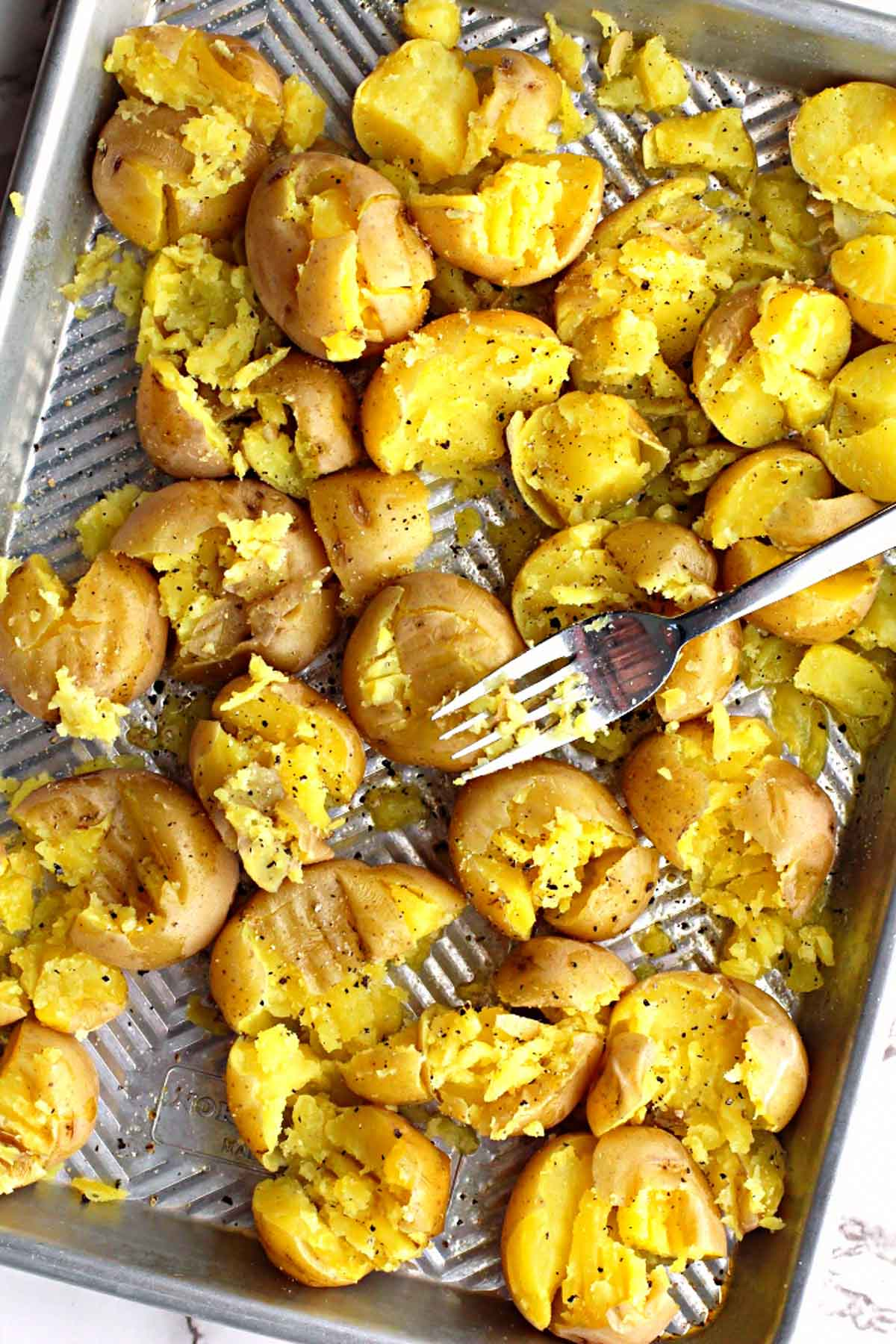 yukon gold potatoes on a sheet pan getting smashed by a fork