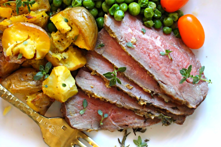 Sliced Tri-tip steak roasted in the oven served with smashed potatoes and peas.