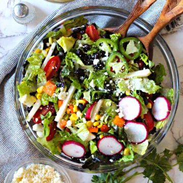 Southwestern Salad Recipe with corn and black beans served in a glass serving bowl with a side of cumin lime honey vinaigrette and cotija cheese